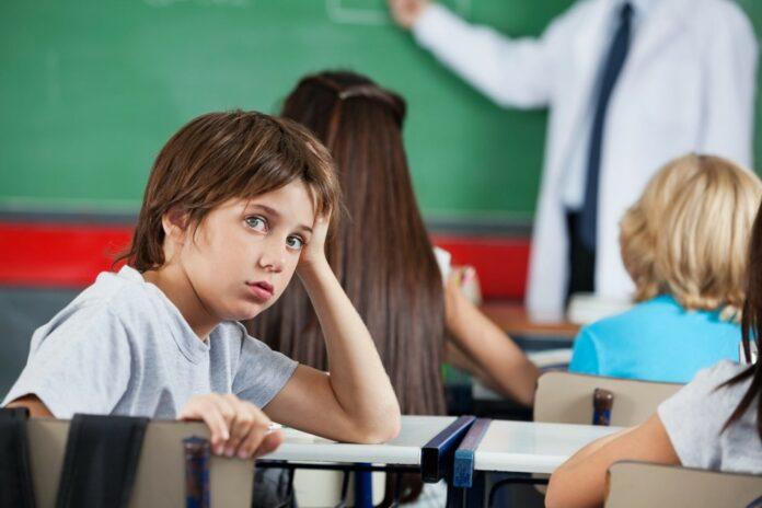 Niño que se encuentra en un salón de clases, sin prestar atención a lo que ocurre en el salón, se nota distraído