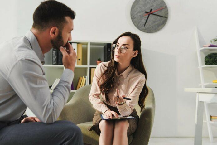 Psicoterapeuta mujer, sentada en sillón con una libreta de notas y pluma en mano, inclinada hacía un hombre que se encuentra sentado de perfil, el hombre tiene la mano sobre su boca con expresión de escuchar de forma atenta.